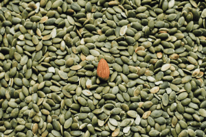 Picture of pumpkin seeds with an almond seeds to boost your health
